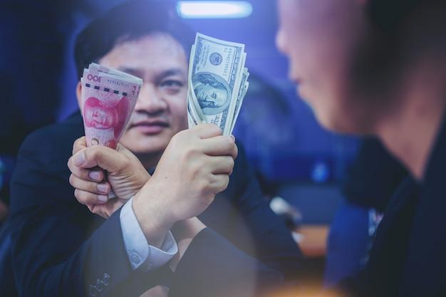 Zakenmanholding dollars en yuan-geld die in het worstelen van de wapen concurreren. handelsoorlog