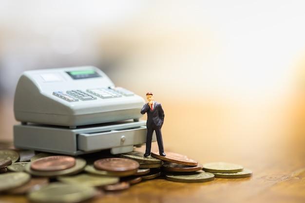 Zakenmanminiatuur die zich op muntstukken en kassiermachinestuk speelgoed bevinden.