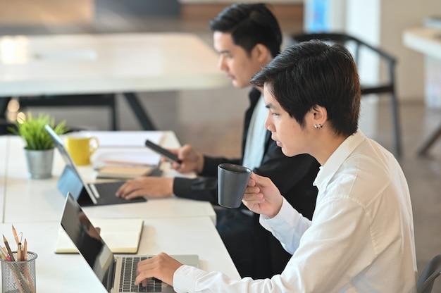 Zakenmanpartner die aan hun concepten in modern bureau samenwerken