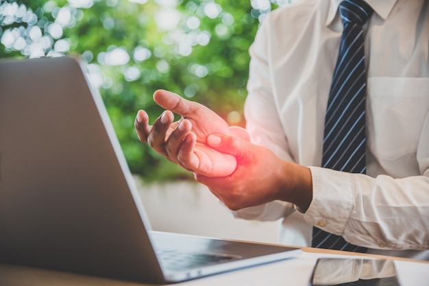 Zakenmanpijn in handen terwijl het woking met laptopt.
