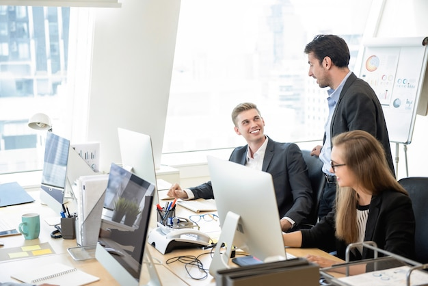 Zakenmansupervisor die met team in het bureau spreken