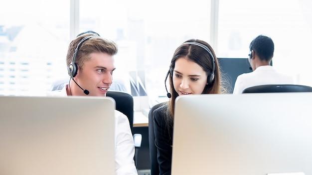 Zakenmantelemarketing personeel die met medewerker in call centrebureau werken
