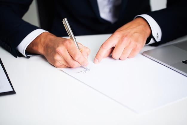 Zakenmanzitting bij bureau die contract ondertekenen