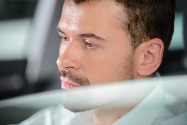 Zakenmanzitting in auto en het glimlachen bij camera.
