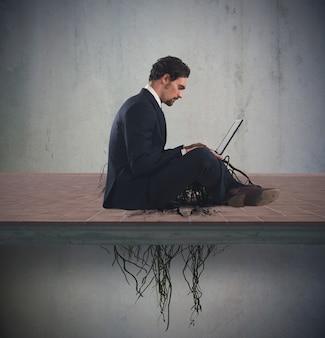 Zakenmanzitting met zijn laptop met onder wortels