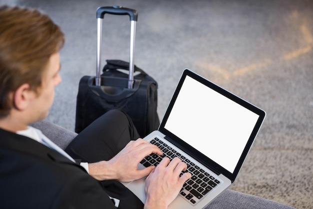 Zakenmanzitting op bank en het gebruiken van laptop in bureau