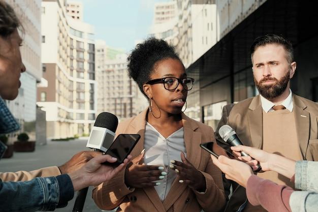 Zakenmensen die in microfoons spreken, geven een interview aan journalisten in de stad buiten