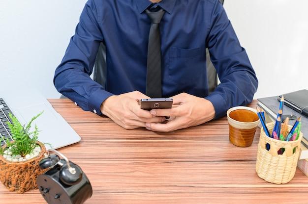 Zakenmensen gebruiken smartphones aan hun bureau in de kamer