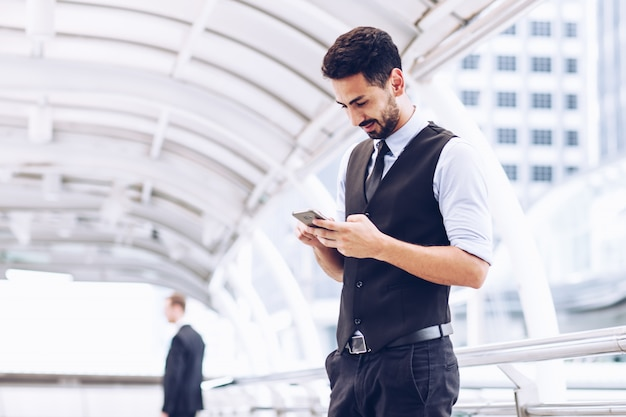 Zakenmensen gebruiken smartphones om auto's te bellen.