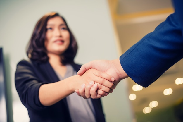 Zakenmensen handen schudden, tussen vergadering in vergaderzaal