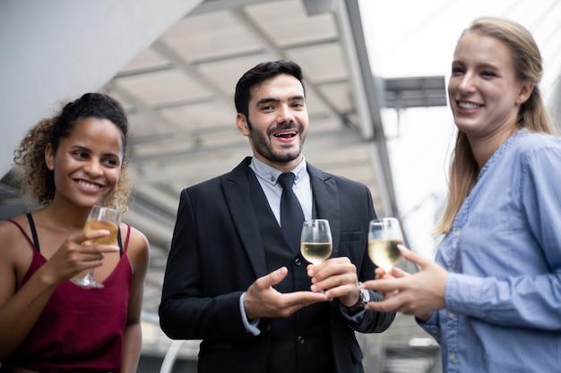 Zakenmensen klinken glazen en drinken wijn om het succesvolle werk te vieren. groep bedrijfsmensen vieren door wijn met glimlach te drinken.
