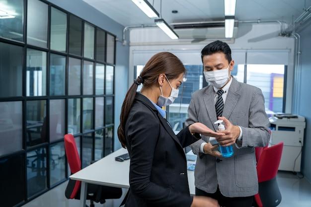 Zakenmensen met gezichtsmaskerbescherming desinfecteren hun handen op kantoor na covid-19 quarantaine.