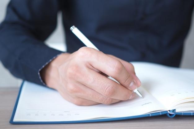 Zakenmensen schrijven informatie in het boek.