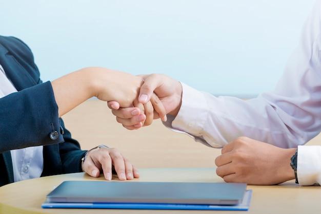 Zakenmensen schudden elkaar de hand na het maken van een overeenkomst