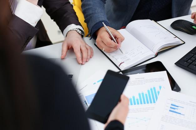 Zakenmensen studeren documenten bespreken problemen schrijven informatie veel papierwerk