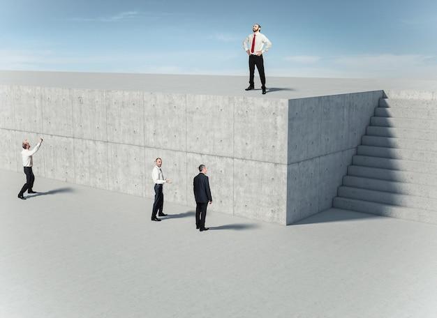 Zakenmensen voor een betonnen muur, een van hen vindt de oplossing en gebruikt de trap. concept van vindingrijkheid en probleemoplossing.