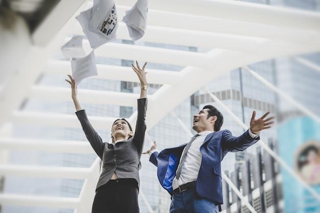 Zakenmensen werpen papieren op terwijl ze voor het kantoorgebouw staan. succesvol bedrijfsconcept.