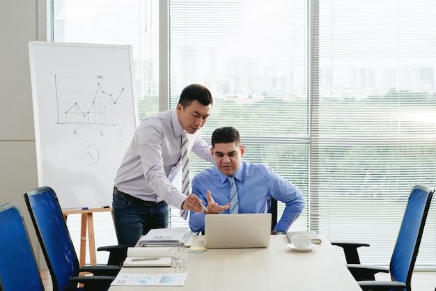 Zakenpartners die het digitale financiële rapport doornemen