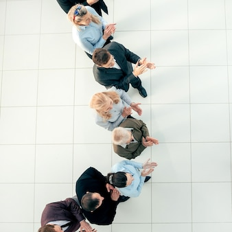 Zakenpartners in bovenaanzicht die voor een grote groep medewerkers staan