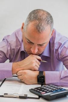 Zakenpersoon die hard over belasting denkt. belasting concept. foto van jonge gedeprimeerde zakenman zitten op kantoor