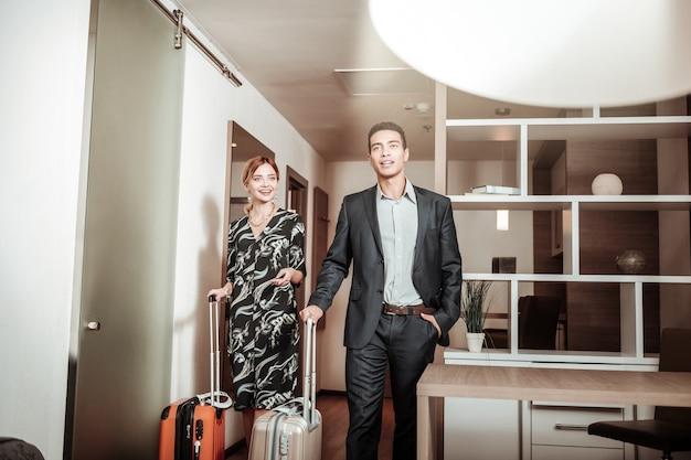 Zakenreis. paar rijke zakenlieden die naar hun hotelkamer komen met een zakenreis