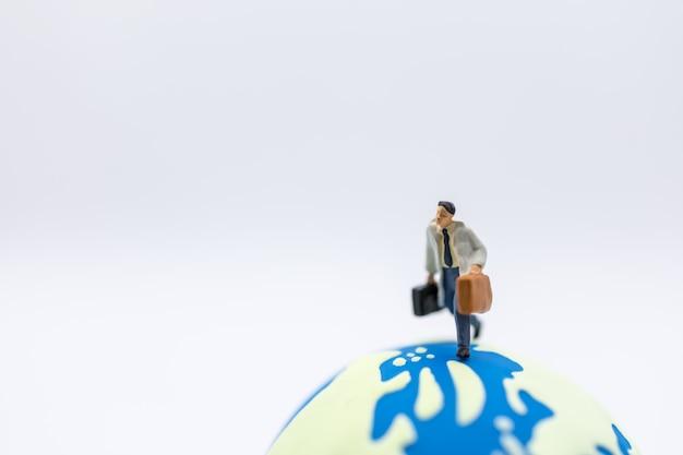 Zakenreizen en wereldwijd concept. sluit omhoog van het miniatuurcijfer van de zakenmanreiziger met bagage die op miniwereldbal lopen
