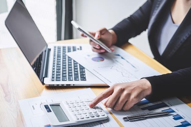 Zakenvrouw accountant werken analyseren en berekenen van kosten financiële jaarlijkse, financiële balansoverzicht en analyseren document grafiek en diagram, financieren maken van aantekeningen op rapport
