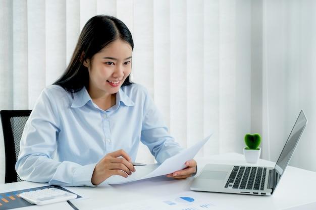 Zakenvrouw analyseert de grafiek en vergadert videoconferenties met laptop op het thuiskantoor voor het stellen van uitdagende zakelijke doelen