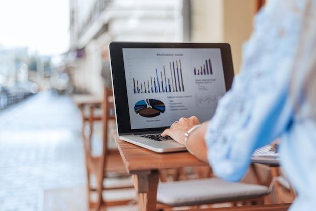 Zakenvrouw analyseren van financiële gegevens zittend aan een tafel in een café
