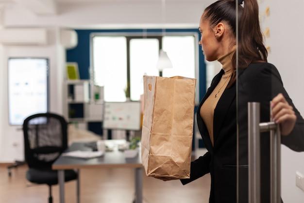 Zakenvrouw arriveert op kantoor met smakelijke heerlijke afhaalmaaltijden in papieren zak voor de lunch in het bedrijfskantoor van de bezorgservice. manager met afhalen fastfood.