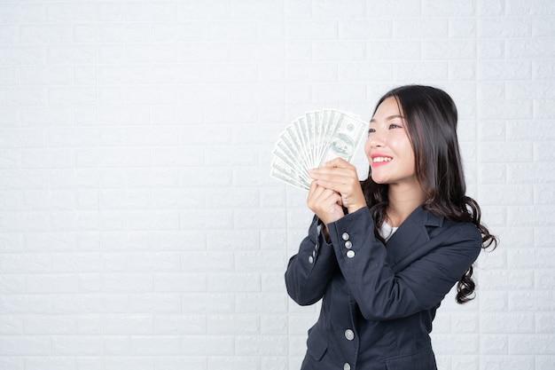 Zakenvrouw bankbiljet, contant geld afzonderlijk, witte bakstenen muur gemaakt gebaren met gebarentaal.