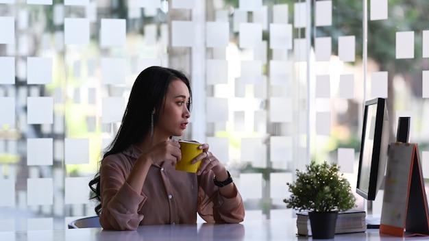 Zakenvrouw bedachtzaam wegkijken en koffiekopje vasthouden terwijl ze op haar werkruimte zit.