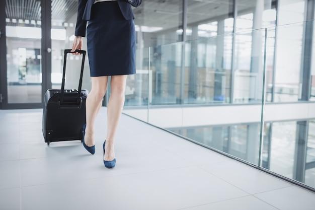 Zakenvrouw bedrijf koffer lopen door kantoor