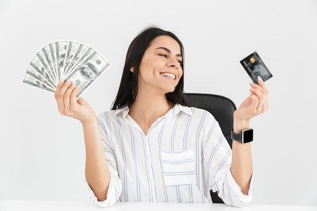 Zakenvrouw bedrijf plastic creditcard en ventilator met dollar geld bankbiljetten zittend in fauteuil in kantoor geïsoleerd over witte muur