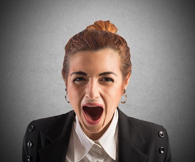 Zakenvrouw beklemtoond en gefrustreerd schreeuwt op het werk