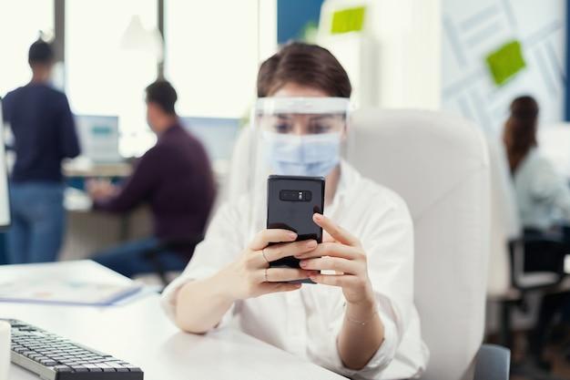 Zakenvrouw bespreken en chatten op smartphone met gezichtsmasker tegen covid19 tijdens wereldwijde pandemie. multi-etnische collega's die werken met respect voor sociale afstand in een financieel bedrijf.