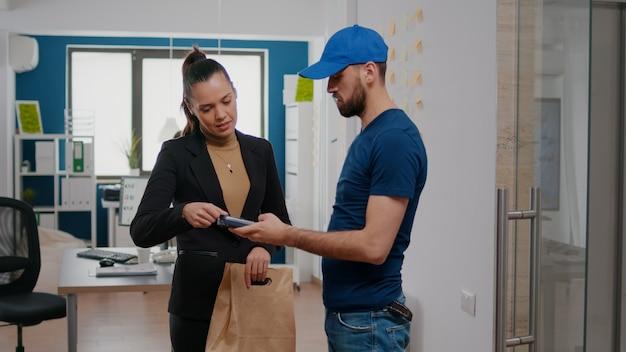 Zakenvrouw betaalt met contactloze creditcard afhaalmaaltijden maaltijdbestelling aan bezorger terwijl ze werkt in het kantoor van een opstartend bedrijf