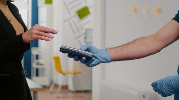 Zakenvrouw betalende afhaalmaaltijden met creditcard tijdens de lunch met behulp van contactloze pos-service service
