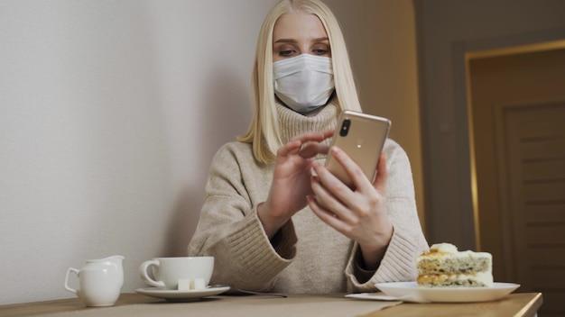 Zakenvrouw bezig met een laptop in een café in een medisch masker, verwijdert. opheffing van quarantainemaatregelen.