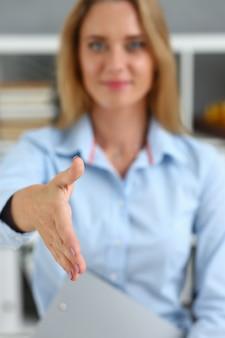 Zakenvrouw bieden hand te schudden als hallo in office close-up.