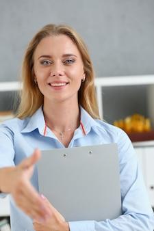 Zakenvrouw biedt hand om te schudden als hallo in kantoor closeu