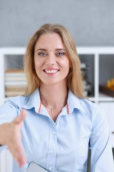 Zakenvrouw biedt hand te schudden als hallo op kantoor