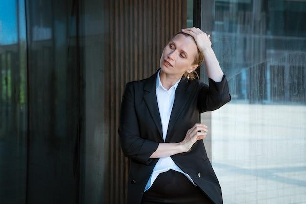 Zakenvrouw blonde in een pak maakt haar haren recht in de buurt van het kantoorgebouw