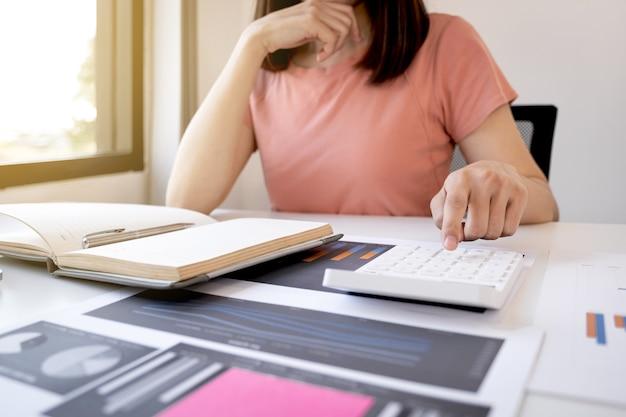 Zakenvrouw boekhouder hand gebruik rekenmachine en analyse van de grafiek met laptop op het kantoor aan huis