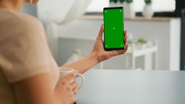 Zakenvrouw browsen op internet met behulp van mock-up groen scherm chroma key smartphone zittend aan een bureau. freelancer die online informatie veegt voor sociale media-projecten met behulp van een geïsoleerd apparaat