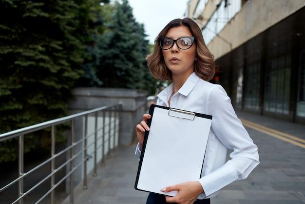 Zakenvrouw buitenshuis met documenten in de hand lichte achtergrond. hoge kwaliteit foto
