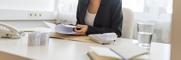 Zakenvrouw consultant zit aan haar bureau kijken naar papierwerk en rapport, met bonnetjes, notities, rekenmachine en glas water op haar bureau.