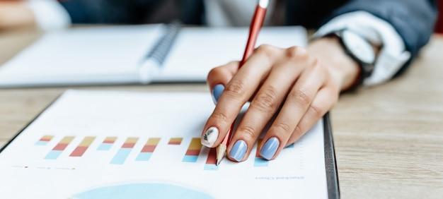 Zakenvrouw controleert grafieken en vernieuwt financiële vooruitgang. het meisje analyseert het bedrijfsmodel op de werkvloer.