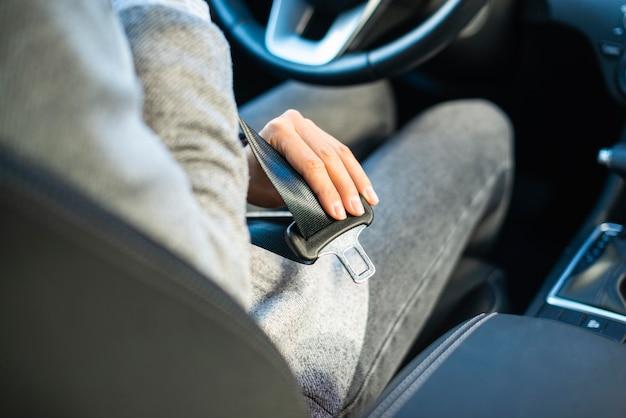 Zakenvrouw de veiligheidsgordel in de auto zetten