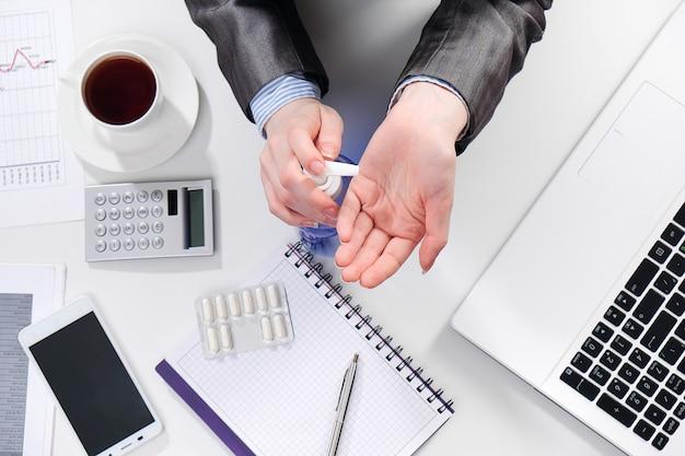 Zakenvrouw desinfecteert haar handen met een op alcohol gebaseerd antibacterieel middel op kantoor